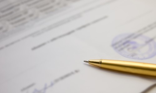 A golden pen on a contract